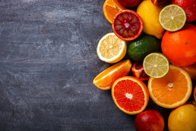 Different citrus fruit on a grey background