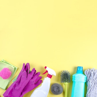 Different cleaning equipments on yellow backdrop