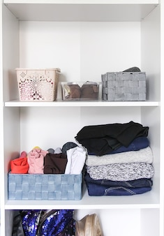Различная одежда в домашнем гардеробе с бумажными заметками. небольшая организация пространства. вертикальное хранение. выкатываемые рубашки в тканевые коробки.