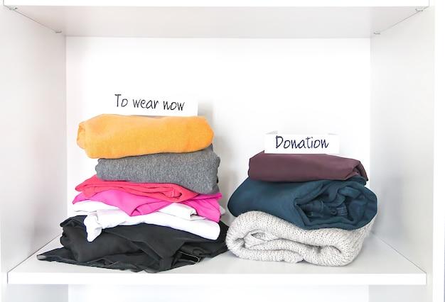 Различная одежда в домашнем гардеробе с бумажными заметками. небольшая организация пространства. вертикальное хранение.