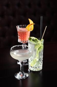 Различные коктейли в баре на вечеринке в ночном клубе. коктейли на черном фоне в стеклянных очках.