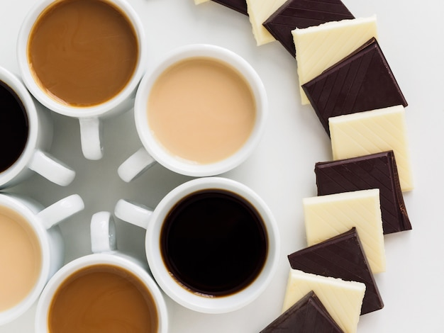 Different coffee in white cups with white and bitter chocolate