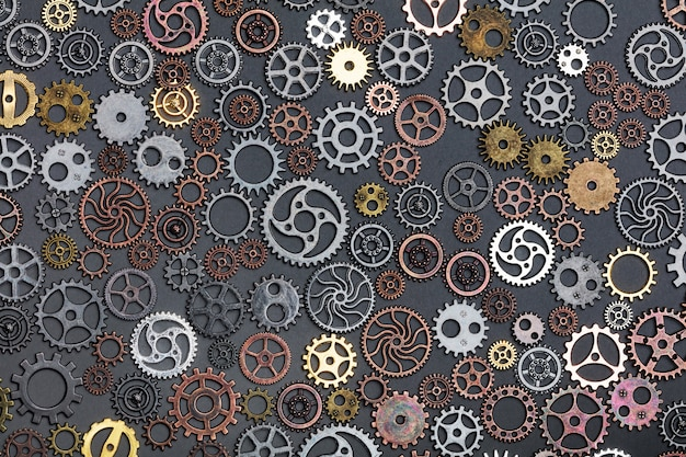 Different cogwheels laying on grey background.