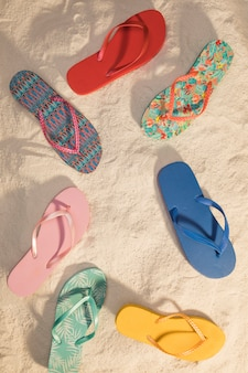 Different color flip flops on beach
