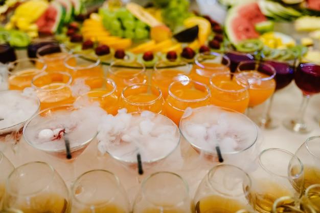 Разноцветные алкогольные коктейли на вечеринке под открытым небом, мартини, водка с пузырьками на свадебном столе. напитки мартини с эффектом дыма сухого льда. коктейль с ледяным паром на барной стойке, крупным планом.