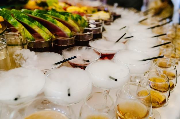 Разноцветные алкогольные коктейли на вечеринке под открытым небом, мартини, водка с пузырьками на свадебном столе. напитки мартини с эффектом дыма сухого льда. коктейль с ледяным паром на барной стойке, крупный план.