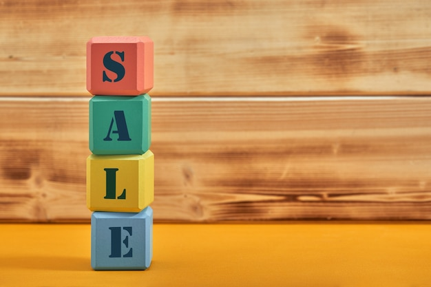 Different colored blocks with the wordings sale, isolated against yellow background.