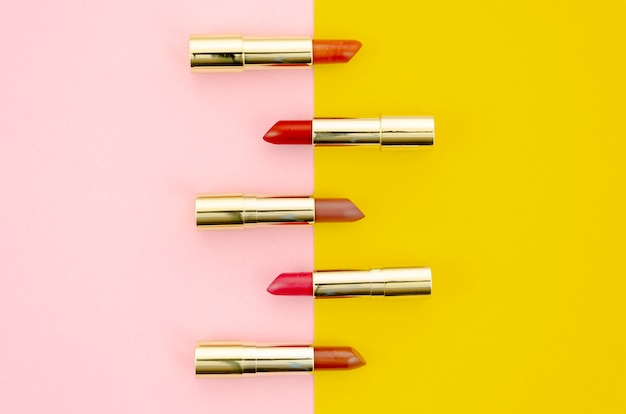 Different colored lipsticks on pink and yellow background