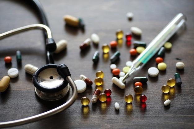 나무 질감 테이블에 있는 다양한 색의 약과 정제