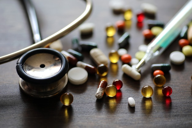 Different colored medications and tablets on a wooden texture table