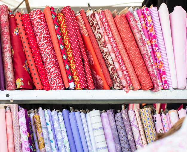Different colored pills of cloth fabrics textile neatly folded for display