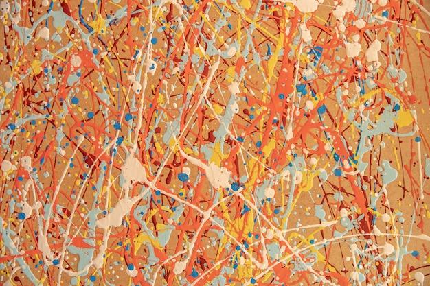 不規則な色の塗布によって作成された黄色の背景に異なる色の斑点