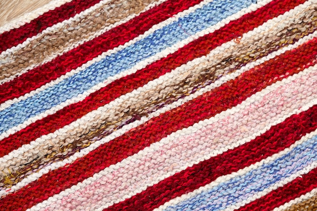 Different colored stripes on the knitted fabric surface. background close-up of textiles retro rugs or rugs. the texture of the fabric is a combination with the geometry of the lines. handmade product