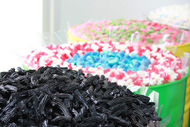 Different colorful candies in big jars or barrels in candy shop.