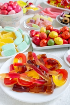 Different colorful flavored fruit candy on plates on a white wooden background. vertical view