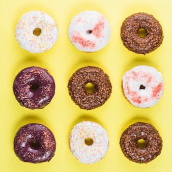 Different colorful frosted doughnuts on yellow background