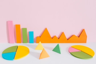 Different colorful graph with pyramid shapes against pink background