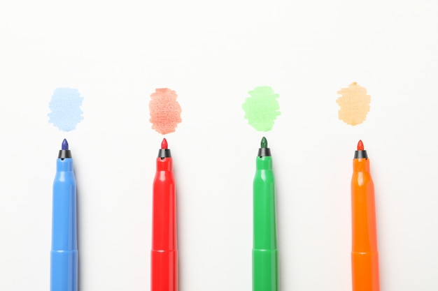 Different colorful markers on white background, top view