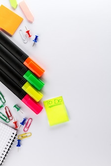 Different colorful markers with business office accessories on white office table. top view.