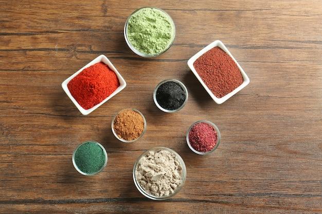 Различные красочные порошки суперпродуктов в мисках на деревянном столе