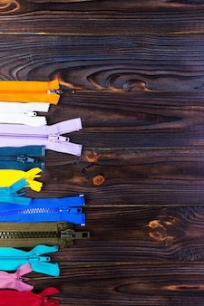 Different colorful zippers in front of wood background