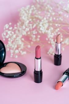 パウダーメイクの女性の装飾的な化粧品とピンクの背景に口紅のさまざまな色