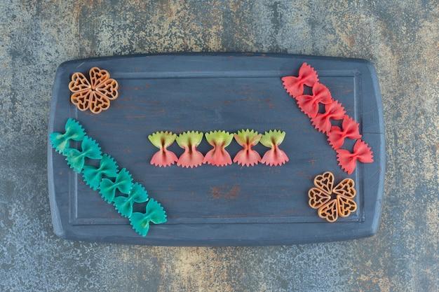 Макароны разных цветов на доске, на мраморном фоне.