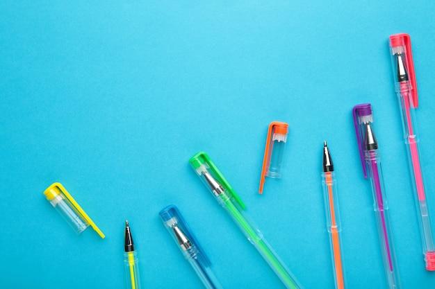 コピースペース付きの青い表面に異なる色のペン