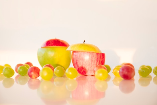Different colors sliced apple with red and green grapes on reflective desk