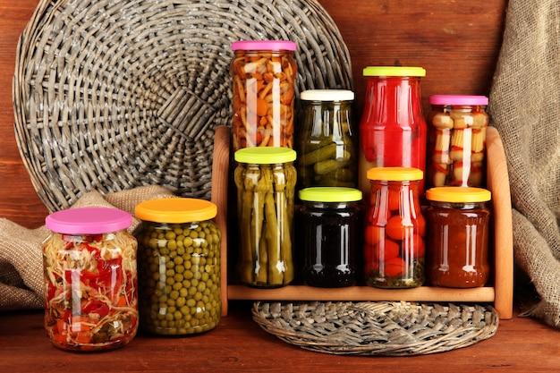 Различные консервы на полках на деревянных фоне Premium Фотографии