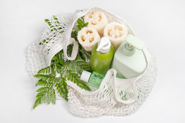 Different containers for lotion, shampoo, conditioner or liquid soap in eco bag. loofah or luffa washcloth, vegetable sponge, alternative to plastic, zero waste, eco friendly.