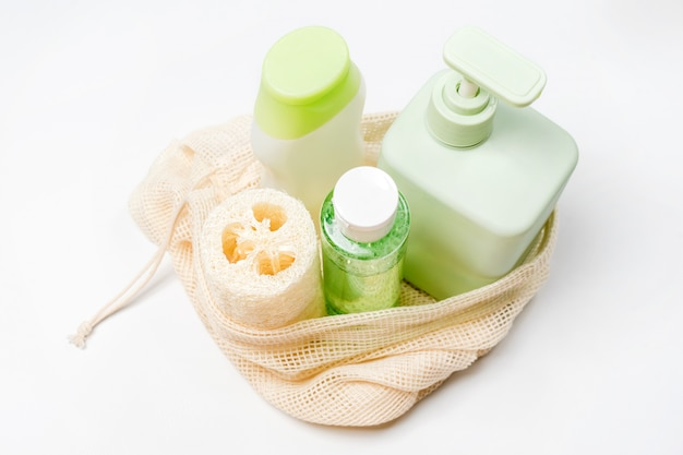Different containers for shampoo, conditioner, tonic, liquid soap in eco bag. natural beauty products