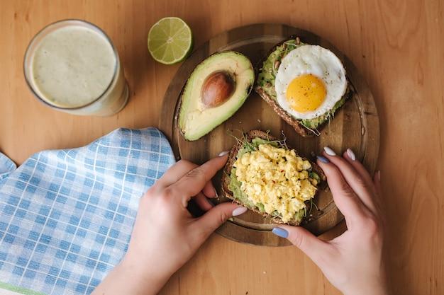 Различное вареное яйцо на бутерброде авокадо с цельнозерновым хлебом на деревянной доске. смузи со шпинатом. вид сверху. концепция веганской еды.