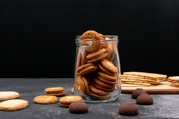 Different cookies in glass jar on dark surface