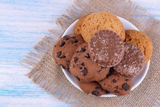 ナプキンと青い木製のテーブルの上のプレートのさまざまなクッキー。焼く。うまい。上からの眺め