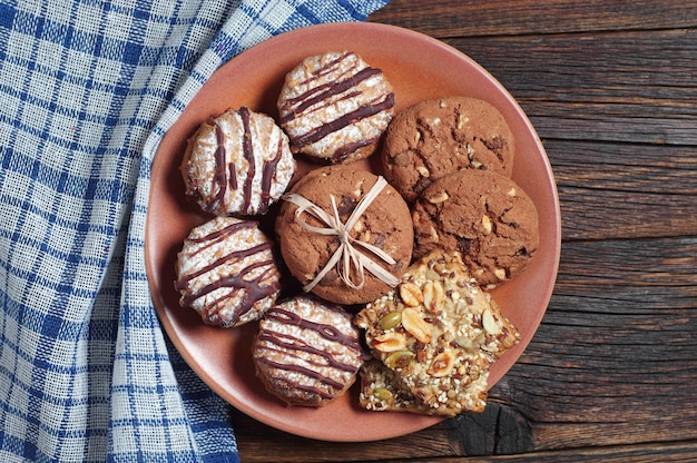 Different cookies in a plate on rustic wooden table with blue tablecloth, top view