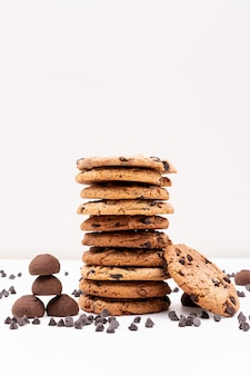 Different cookies with chocolate pieces on white surface