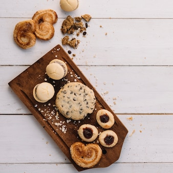 Different cookies on wooden board