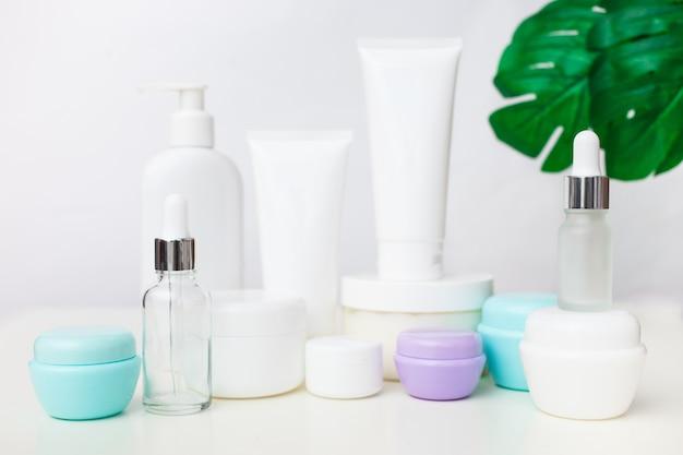 Различные косметические бутылки на белом фоне с листьями. набор косметических средств. сборник косметических пакетов для кремов, супов, пенок, капельниц.