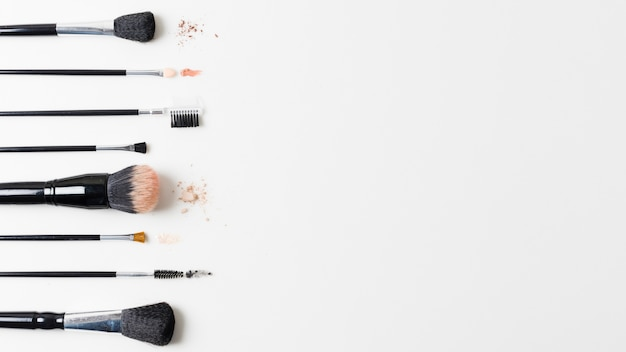 Different cosmetic brushes arranged on white background