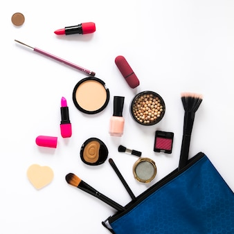 Different cosmetics scattered from beauty bag on table