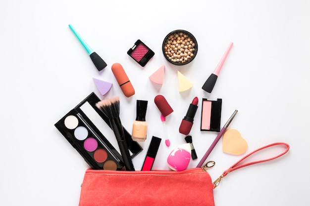 Different cosmetics scattered from red beauty bag