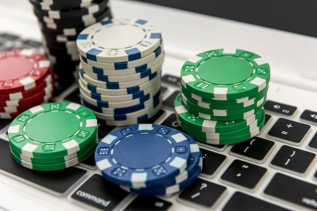 Different of cost casino chips stacking on a laptop