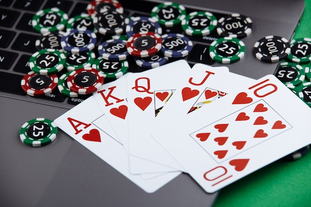 Different of cost casino chips stacking and playing cards on a laptop. bet at game and win.