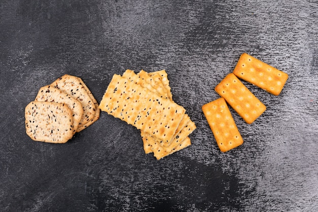Different crackers top view on dark surface