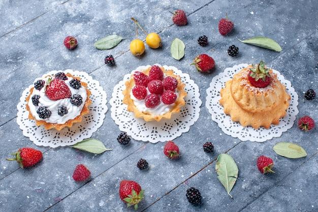 明るい机の上の新鮮な果物と一緒にベリー、ベリーの新鮮な果物とさまざまなクリーミーなケーキ