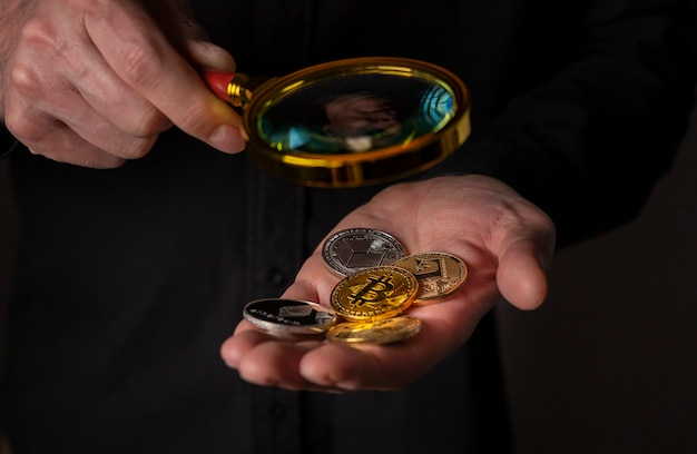 Различные монеты криптовалюты в руке с лупой крупным планом кучу биткойнов и других криптовалют ...