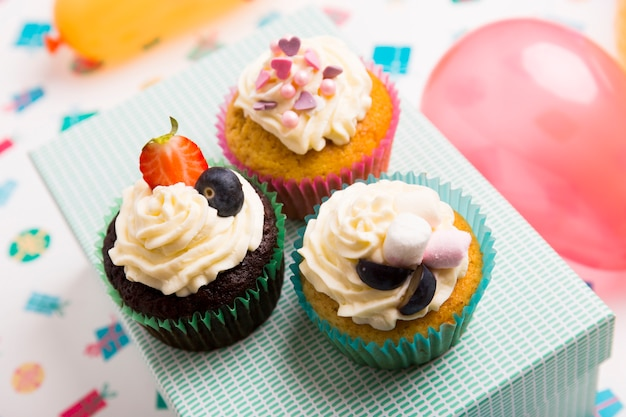Different cupcakes with berries on box