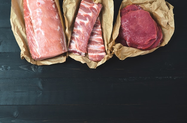 Different cuts of meat, fresh on a dark background. copy space.