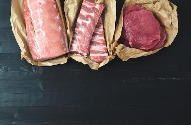 Различные куски мяса, свежие на темном фоне. скопируйте пространство.